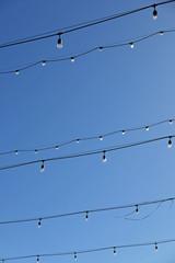 Lichterketten an blauem Tageshimmel