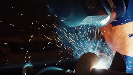 Welder at work in metal industry. Clip. Welder at work in factory. Welder welding a metal in workshop