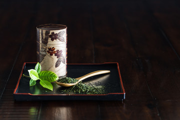 Cherry tree bark Tea Canister, wooden spoon and green tea on Japanese tray.