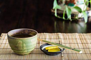 Green tea cup and Chopstick on bamboo mat.