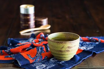 Green tea cup on Japanese wrapping cloth (furoshiki) on rustic wood table.
