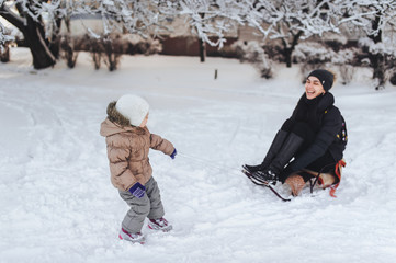 A little girl tries to ride her mom on a sled. Adults ride a sled. Joke, comic picture. Winter entertainment. Mom plays with her daughter.