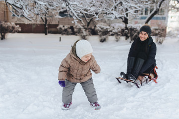 A little girl tries to ride her mom on a sled. Adults ride a sled. Winter entertainment. Mom plays with her daughter. Joke, comic picture.