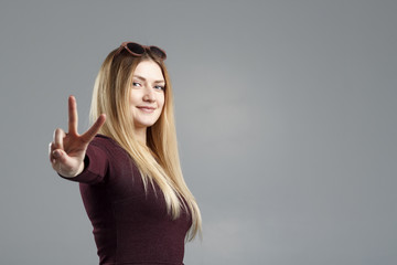 Closeup portrait of happy excited successful young woman giving peace, victory or two sign isolated on light green background. Positive emotions face expressions feelings attitude reaction perception