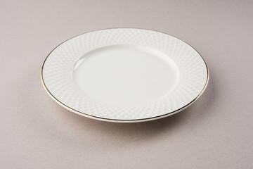 Empty white ceramic round plate isolated on white background