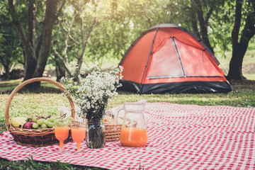 Healthy food and accessories outdoor summer or spring picnic, Picnic wicker basket with fresh fruit, bread and a glass of refreshing orange juice in the camping nature background