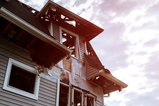 Rescuers firefighters extinguish a fire on the roof. The building after the fire. Burnt window. Ruined house. Catastrophe.