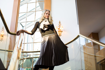 Portrait of Woman Standing on Nice Luxury Stairwell While Holding Skirt
