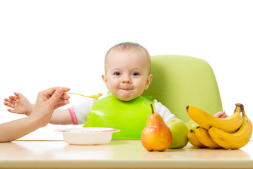 Baby having a table full of healthy food. Cheerful toddler with fruits apples, bananas, pear. Isolated on white