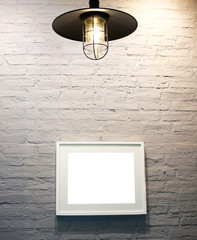 Picture frame with empty photo hanging on a white brick wall with ceiling light.