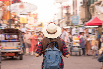 Young Asian woman with hat and backpack traveling in Khaosan Road among people, walking outdoor market in Bangkok, Thailand.