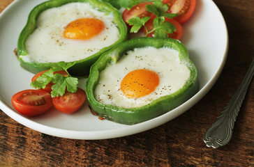 Fried egg in the ring of the bell peppers with herbs