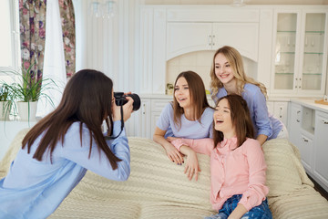 A group of friends of young girls are photographed on a camera at a meeting in a room indoors.