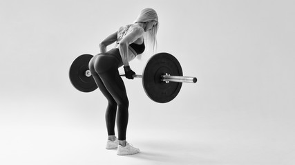 Confident young woman doing weight lifting workout at gym turning back Attractive young woman bodybuilder lifting barbells looking focused Horizontal black and white concept photo