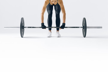 Fitness attractive woman preparing to practice deadlift with heavy weights Female bodybuilder doing heavy weight lifting work out on white background Close-up horizontal picture