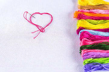 Colored thread for embroidery on white canvas, a needle with red thread in the shape of a heart. The concept of love for a hobby. Copy spase