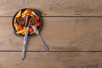 Sliced beef with potatos and tomatos