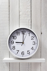 wall clock at wooden shelf