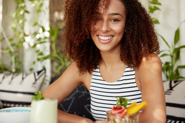 Horizontal shot of dark skinned cheerful young female with curly hair, enjoys spare time at weekend in cafe, eats delicious cocktail. African American woman glad to spend vacations with friends