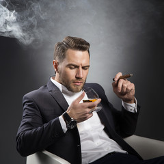 Man with cognac and cigar wearing uit and perfect modern hair style over grey background