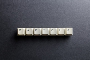 Word captcha made using computer keyboard buttons on a black background. Compact disk. IT technology concept.