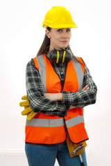 Construction work and home improvement jobs concept with a caucasian brunette mature woman wearing jeans, hard hat, tool belt and other safety equipment, isolated on white with clipping path