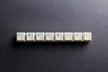 Word freeware made using computer keyboard buttons on a black background. No monetary cost free software. IT technology concept.