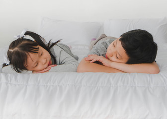 Asian Sister sleeping with his brother in white bedroom.Concept of happy family.