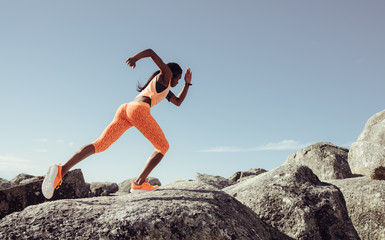 Female runner running over big rocks Wall mural