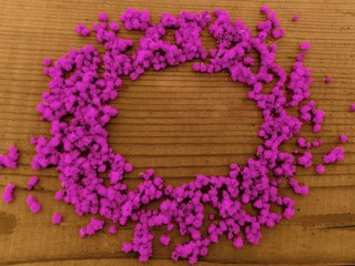 Round pink flowers frame. Round frame of purple pink little flowers on wooden background. Text plase in round frame of pink-purple little flowers on wooden table. Top view of round pink flowers frame