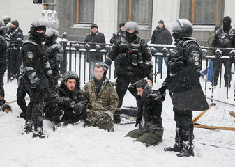 Riot police detain anti-government protesters near the parliament building in Kiev