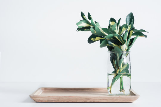 Small glass vase with yellow-green leaves on bamboo tray