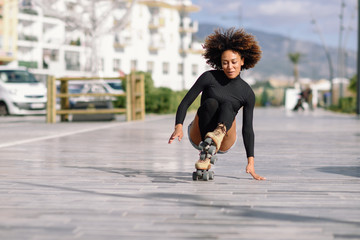 Black woman on roller skates falling to the ground.