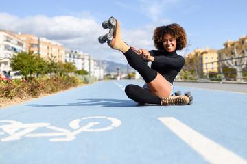 Funny smiling black girl sitting on bike line and puts on skates.