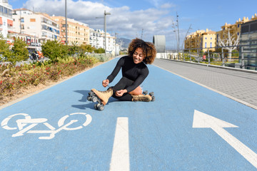 Young smiling black girl sitting on bike line and puts on skates.