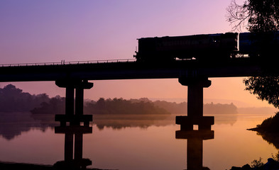Train passing by on a bridge on water. It made for a good silhouette