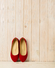 Red women's shoes (ballerinas) on wooden background.