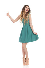 Beautiful Young Woman In Green Mini Dress And High Heels Is Showing Thumb Up And Laughing