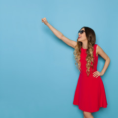 Beautiful Young Woman In Red Dress Is Posing With Fist Raised.