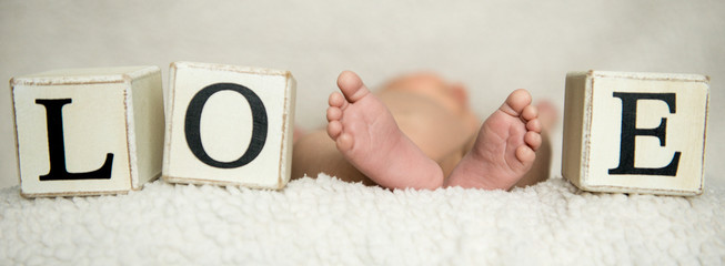 Children's feet. Tiny legs of a newborn baby Concept of a happy family. Beautiful conceptual image of motherhood.