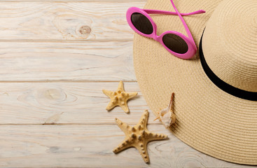 Beach summer concept. Female hat and pink sunglasses on a light wooden background.