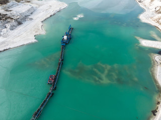 Aerial view of the long boom of a suction excavator in a quartz quarry for the excavation of white sand.