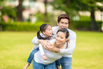 Cute Asian girl on neck parents big happy laughing and run around together.Happy family piggybacking adorable little daughter is smiling.