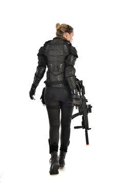 full length portrait of female  soldier wearing black  tactical armour, standing  with back to the camera holding a gun, isolated on white studio background.