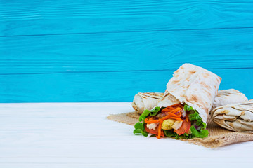 Delicious shawarma sandwich on wooden background