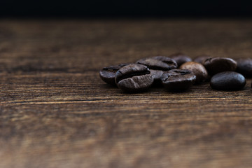 Coffee beans on a dark background and a wooden table. Closeup.
