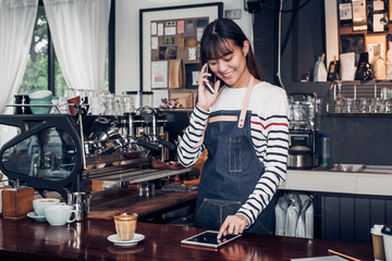 woman barista take order by mobile and tablet,asia female waitress using digital device in coffee shop business at counter bar in cafe,modern food owner business start up.