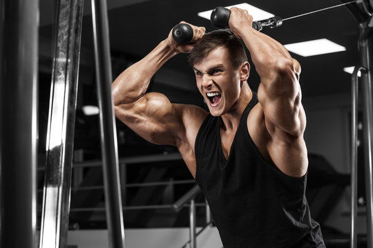 Muscular man working out in gym, bodybuilder strong male
