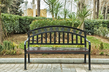Black iron chair . Black bench on the street . Bench in Park on a background of brick green tree