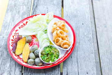 The delicious pork scratching or pork crackling snack food Thai tradition cuisine menu with herbs, yam or sweet potato boiled, cabbage, chili youth local popular meal in Chiangmai, Thailand.
